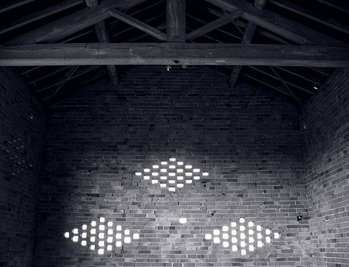 Interior of an old brick barn, illuminated by dove holes cut in the side of the walls, Meon Hill